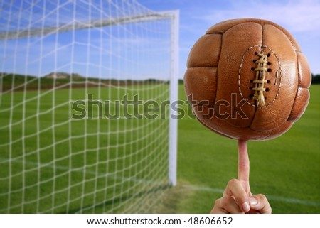 Football vintage ball in hand net soccer goal green grass background [Photo Illustration]