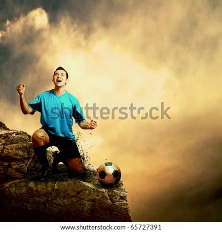 Footballer on the top of mountain - stock photo