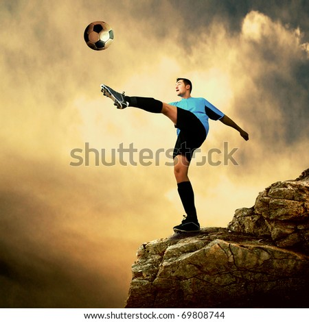 Footballer on the top of mountain - stock photo