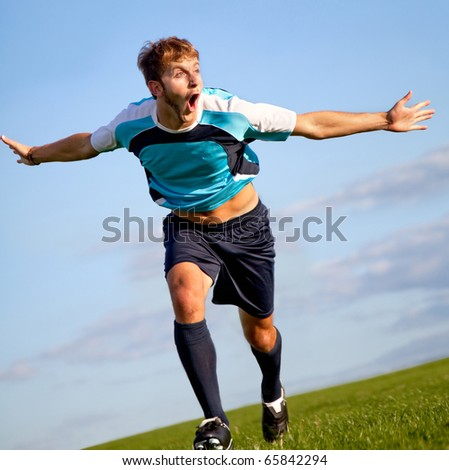 Footballer running on the field celebrating a goal - stock photo