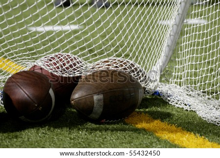 Footballs on a field of grass in front of a white net with room for text. - stock photo