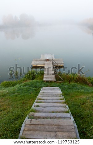 Footbridge and lake in fog - stock photo