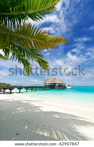 footbridge connecting with the thatched jetty in maldives island resort - stock photo