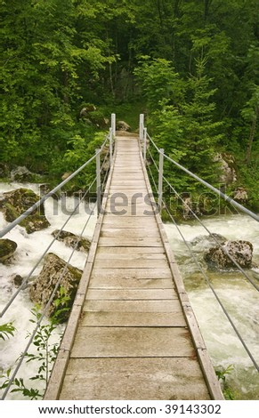 Footbridge crossing the river in the forest - stock photo
