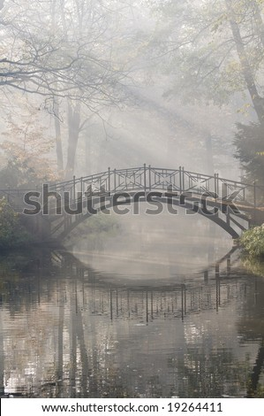 footbridge in a foggy park - stock photo