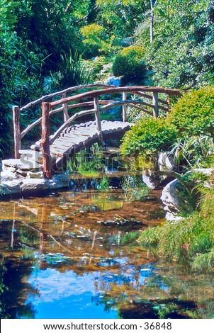Footbridge over pond - stock photo