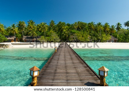 footbridge over turquoise ocean to an maldivian island - stock photo