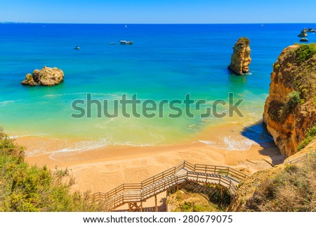 Footbridge walkway on Dona Ana beach with turquoise sea water, Algarve region, Portugal - stock photo