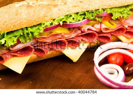 Footlong Salami, Ham, cheese sub with lettuce, tomato, onion and peppers - stock photo