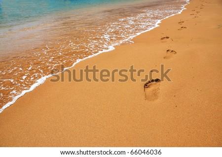 Footmarks on a sandy beach - stock photo