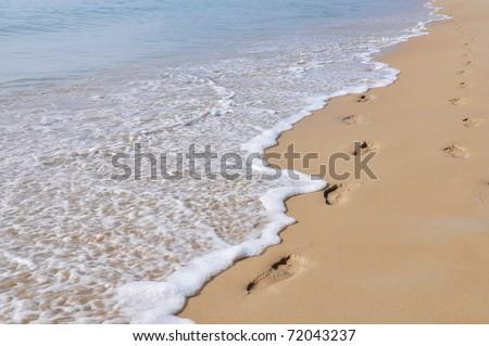 Footmarks on the sandy beach - stock photo