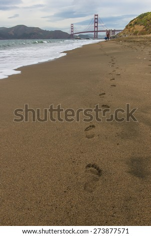 Footorint on the sand to Golden Gate Bridge - stock photo
