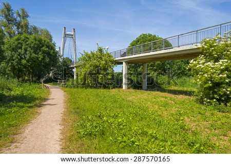 Footpath along a bridge over a canal in spring - stock photo