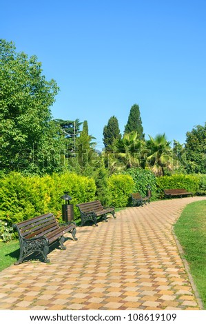 Footpath and wooden benches in a beautiful tropical park in the summer - stock photo