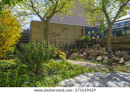 Footpath in a sunny garden in spring - stock photo