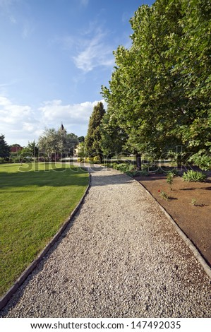 Footpath in the park with church in the distance - stock photo