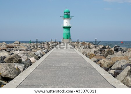 footpath on pier leading to breakwater light or beacon at Rostock Warnemunde, Germany - stock photo