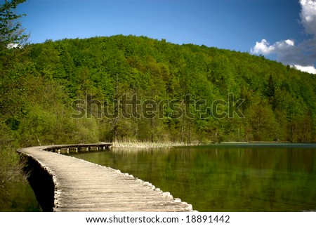 footpath over clear mountain lake in national park of plitvice, croatia - stock photo