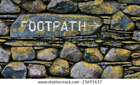 Footpath sign on stone wall with yellow lichen - stock photo