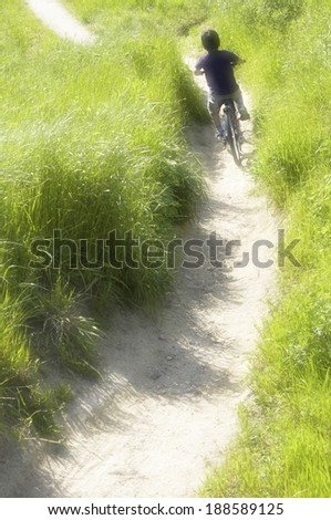 Footpath with young Asian boy riding bike