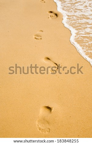 Footprint in the yellow sand on the beach - stock photo