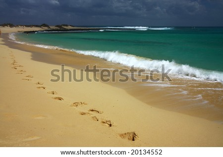 footprint on sandy beach close to water - stock photo