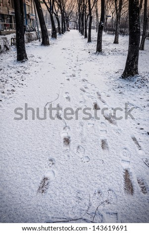 Footprint on snow cover in city in the morning - stock photo
