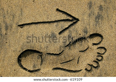 Footprint outline and arrow in the sand