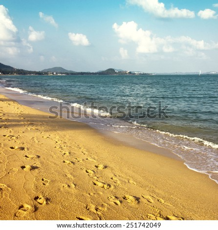 footprint shadow on the beach background. gold sand and sea - stock photo