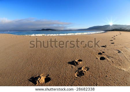 Footprints at dawn on beach by ocean with sun rising over mountain