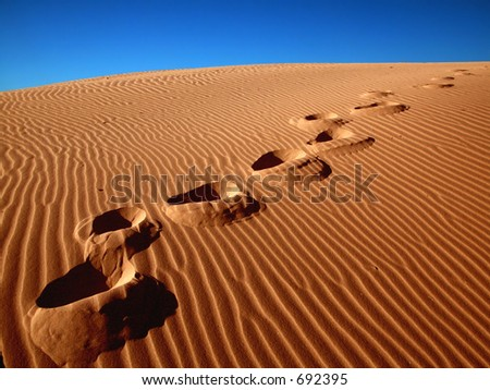 Footprints going over the sand. - stock photo