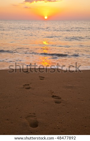 Footprints going towards the sea - stock photo