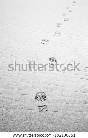 Footprints hiking boots on beach. Monochrome - stock photo