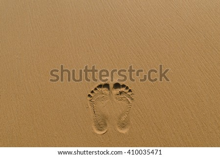 footprints in sand on the beach - stock photo