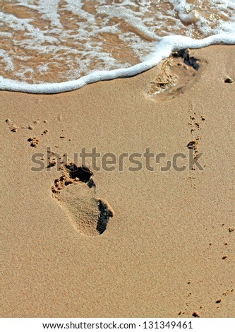 Footprints in send on a beach leading into water.