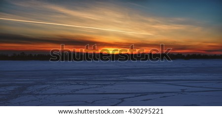 Footprints in the frozen river at sunset - stock photo