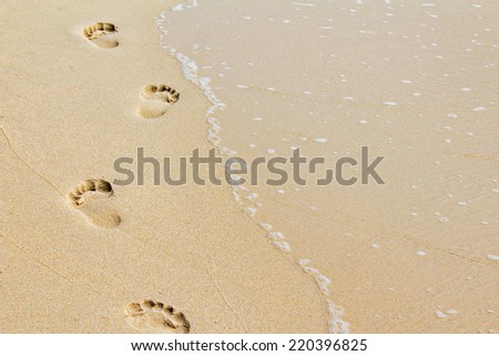 Footprints in the sand along the coast - stock photo