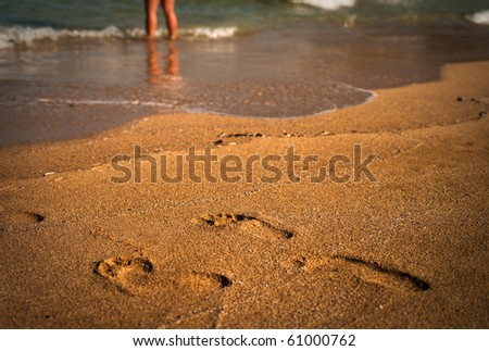 Footprints in the sand. Defocused legs in the background. - stock photo