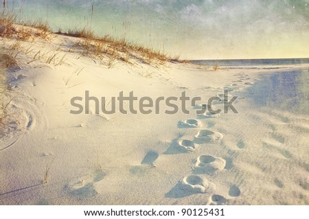 Footprints in the sand dunes leading to the ocean at sunset. Soft artistic treatment with canvas texture, grain and brush strokes added for effect. - stock photo