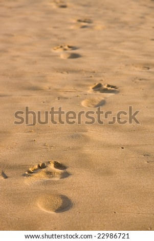 Footprints in the sand leading forward into the distance - stock photo