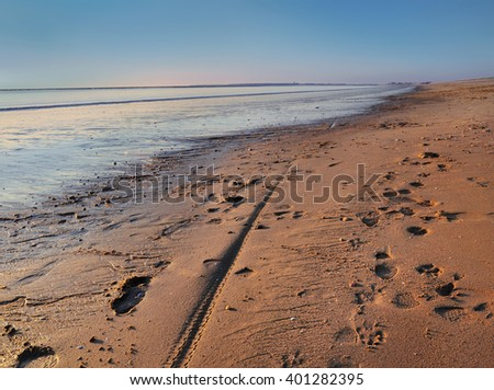 footprints in  the sand of a beach at dusk - stock photo