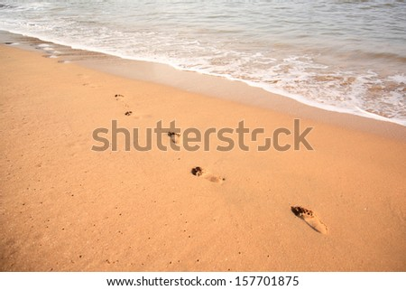 Footprints in the sand on the beach Goa India - stock photo