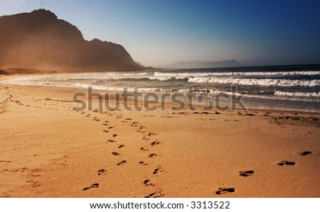 Footprints in the sand on the beach. Shot on a sunny day with a mountain and blue skies in the background. - stock photo