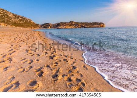 Footprints in the sand on the famous Turkish beach Patara. Colorful sunset in the Turkey,  District of Kas, Antalya Province, Asia. Artistic style post processed photo. - stock photo