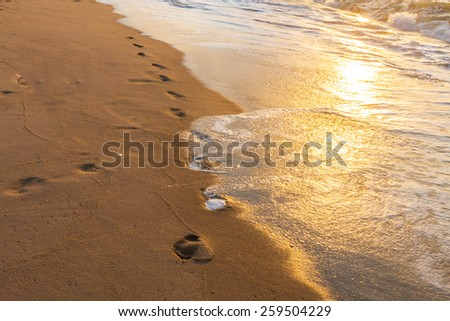 Footprints in the Sand reflective  at sunset time for background - stock photo