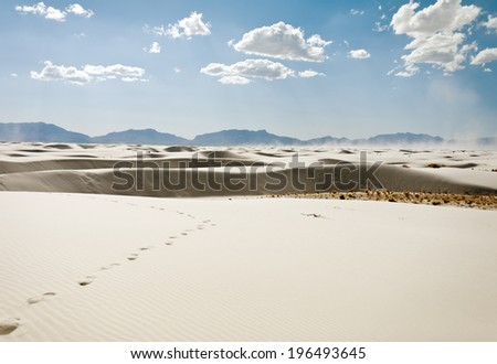 Footprints lead through white sand on a partly cloudy day. - stock photo