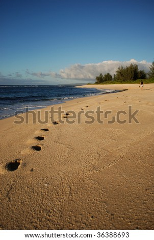 Footprints left by girl on the beach in Oahu, Hawaii.