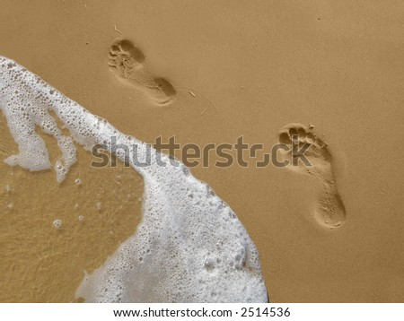 Footprints on a beach with ocean water. - stock photo