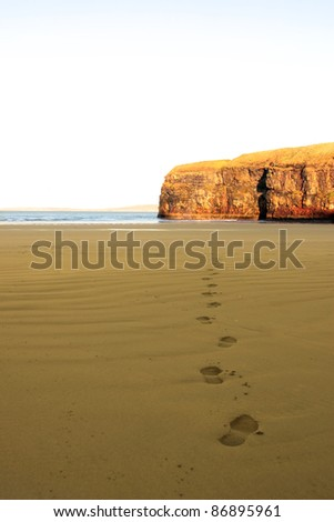 footprints on an empty beach on a beautiful winters day - stock photo