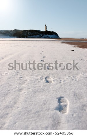 footprints on an empty beach with castle in background on a cold winters day - stock photo